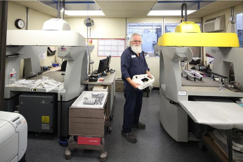 An SKS employee standing in the QC Metrology Lab at SKS